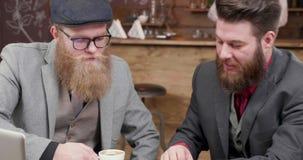 Twee modieuze mannetjes genieten van koffie tijdens een commerciële vergadering stock video