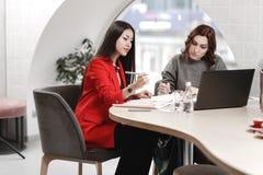 Twee modieuze meisjes binnenlandse ontwerpers die in het bureau bij het ontwerpproject werken royalty-vrije stock fotografie