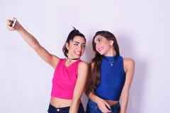 Twee modieuze vrouwen die een selfie nemen Het concept van de vriendschap Stock Foto
