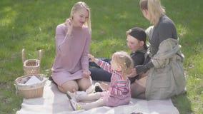 Twee moeders op de deken in het park met hun kinderen Oudere blonde jongen die op de deken, een leuk meisje binnen liggen stock video