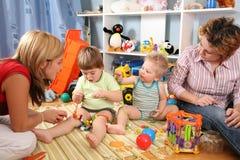 Twee moeders spelen met kinderen in speelkamer 2 Stock Foto's