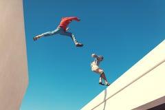 Twee moedige mensen die over het dak springen stock foto