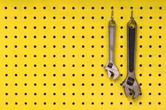 Twee moersleutels hangen van haken op gele pegboard royalty-vrije stock foto