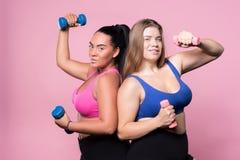 Twee mollige vrouwen die met domoren uitoefenen stock afbeelding