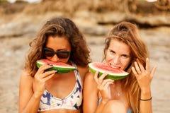 Twee mooi sportief surfermeisje bij het strand royalty-vrije stock afbeelding