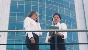 Twee mooie bedrijfsvrouwen die hun werk en één van hen bespreken wordt onderbroken door een telefoongesprek stock footage
