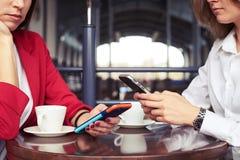 Twee mooie bezige wijfjes die aan smartphones werken royalty-vrije stock afbeeldingen