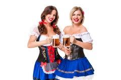 Twee mooie blonde en donkerbruine meisjes van meest oktoberfest bierstenen bierkroes Stock Afbeeldingen