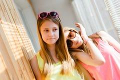 Twee mooie blonde tieners die pret het gelukkige glimlachen hebben Stock Foto