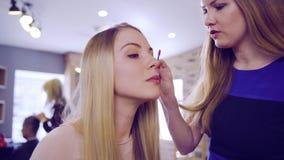 Twee mooie blondevrouwen bij schoonheidssalon bij de spiegel stock video