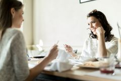 Twee mooie dames die in een restaurant eten terwijl het hebben van een conve Stock Foto's