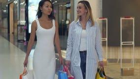 Twee mooie dames die van hun het winkelen weekend genieten stock footage