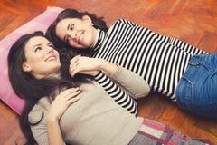 Twee mooie en meisjes die terwijl het liggen op vloer spreken roddelen stock afbeelding
