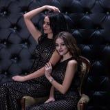 Twee mooie gelooide meisjesmodellen met donker haar zitten op één leunstoel op een zwarte achtergrond met bergkristallen Artistie Stock Afbeeldingen