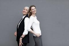 Twee mooie glimlachende vrouwen die zich verenigen Royalty-vrije Stock Afbeelding
