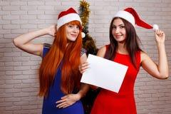 Twee mooie glimlachende vrouwen in Kerstmankappen met lege raad in Ha royalty-vrije stock fotografie