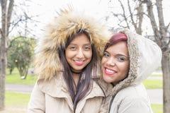 Twee mooie glimlachende vrouwenvrienden in het park royalty-vrije stock afbeeldingen