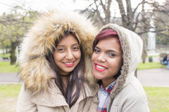 Twee mooie glimlachende vrouwenvrienden in het park royalty-vrije stock foto's