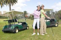 Twee mooie golfspeler met haar golfauto's Royalty-vrije Stock Foto