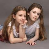Twee mooie, grappige vrienden, 9 jaar oud, op een fotospruit in de studio stock afbeeldingen