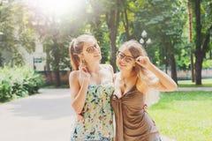 Twee mooie jonge boho elegante modieuze meisjes die in park lopen Stock Fotografie