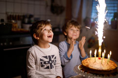 Twee mooie jonge geitjes, kleine peuterjongens die verjaardag vieren en kaarsen blazen stock fotografie
