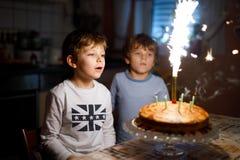 Twee mooie jonge geitjes, kleine peuterjongens die verjaardag vieren en kaarsen blazen stock foto