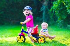 Twee mooie jonge geitjes op een fiets royalty-vrije stock afbeelding