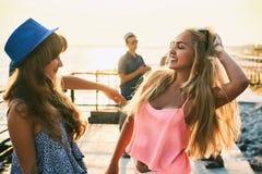 Twee mooie jonge meisjes die pret hebben bij de avondkust met groep hun vrienden op achtergrond stock fotografie