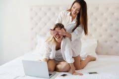 Twee mooie jonge meisjes die pret op bed hebben Royalty-vrije Stock Afbeeldingen