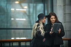 Twee mooie jonge meisjes die in warme kleren het werk aangaande een tablet bespreken Stock Afbeelding
