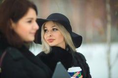 Twee mooie jonge meisjes in het warme kleren lopen Royalty-vrije Stock Afbeeldingen