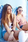 Twee mooie jonge meisjes op de vloer van een lege pool Stock Fotografie