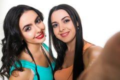 Twee mooie jonge meisjes op een witte achtergrond die selfie maken Stock Foto's