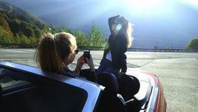 Twee mooie jonge modieuze meisjes nemen foto's op een smartphone binnen een convertibel rood Grappige fotospruit op vakantie stock videobeelden