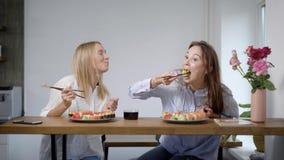 Twee mooie jonge sushi eten rolt en meisjes die, vrienden samen in keuken spreken stock videobeelden