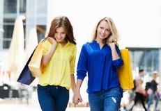 Twee mooie jonge vrouwelijke vrienden die holdingshanden lopen Stock Foto's