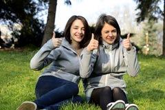 Twee mooie jonge vrouwen die duimen geven ondertekenen omhoog Stock Afbeeldingen