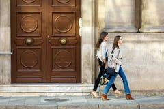 Twee mooie jonge vrouwen die en in de straat lopen spreken Royalty-vrije Stock Fotografie
