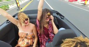 Twee mooie jonge vrouwen die hun wapens opheffen omhoog terwijl het berijden in convertibel stock video