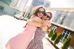 Twee mooie jonge vrouwen die pret in de stad hebben royalty-vrije stock afbeeldingen