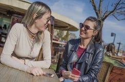 Twee mooie jonge vrouwen die pret hebben in openlucht terwijl het gebruiken van hun mobiele telefoons Stock Afbeeldingen