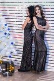 Twee mooie jonge vrouwen modeles in zwarte avondjurken bevinden zich dichtbij een wit die rooster in een Nieuwjaarstijl wordt ver Royalty-vrije Stock Fotografie