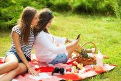 Twee mooie jonge vrouwen op een picknick die het smartphonescherm bekijken stock afbeelding