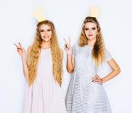 Twee mooie jonge vrouwen vieren partij tonen overwinningsteken op witte achtergrond Beste vrienden die modieuze avond dragen Royalty-vrije Stock Foto's
