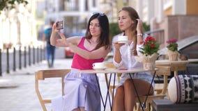 Twee mooie jonge vrouwen zitten bij een lijst in een koffie en nemen een selfie op de telefoon4k langzame motie stock footage