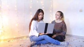 Twee mooie jonge vrouwen zitten op vloer in woonkamer en kiezen giften voor verwanten aan vakantie door laptop stock footage