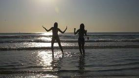 Twee mooie jonge wijfjes die en pret op een strand in langzame motie hebben dansen stock videobeelden