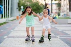 Twee mooie kleine zusters in rolschaatsen Royalty-vrije Stock Afbeelding