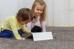 Twee mooie kleine zusters zitten bij een lijst en spelen op een tablet stock foto